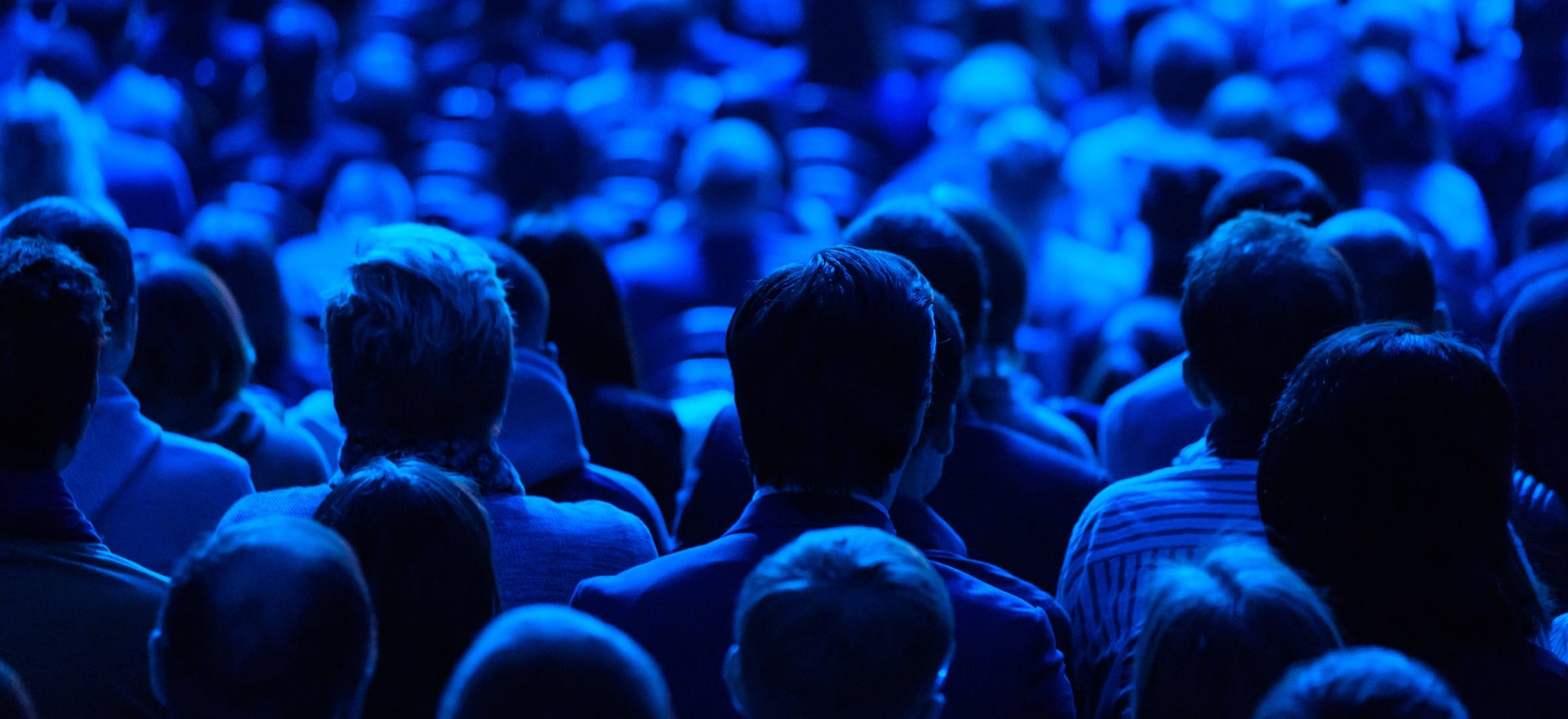 People standing in a crowd looking in the same direction. ominous blue light on them
