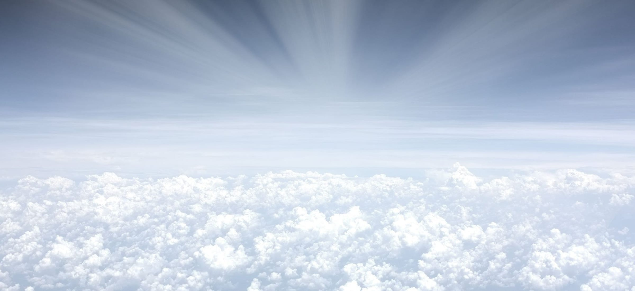 a sky from above the clouds with light radiating