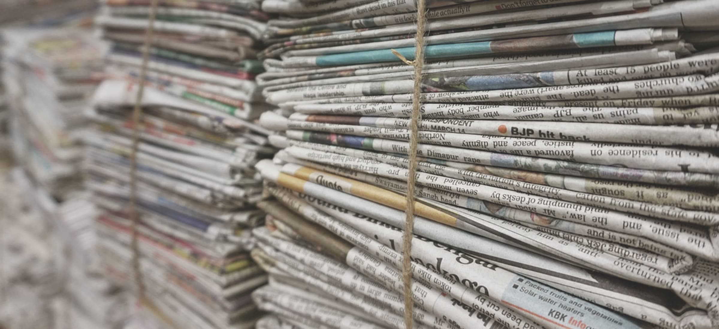 Banner - Stack of news papers for StatePoint Media