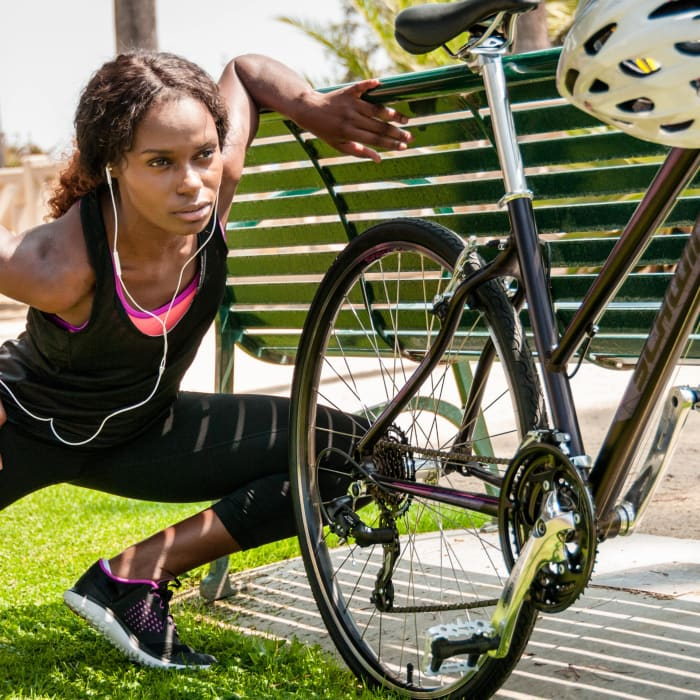 woman stretching next to a Schwinn Bike