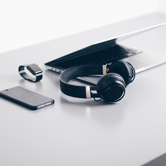 photo- a metal desk with a laptop, headphones, phone and apple watch laying neatly in the center of the table
