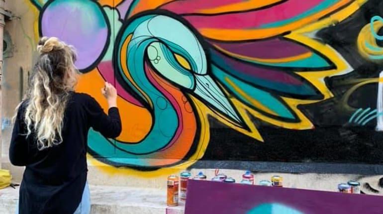 סיור גרפיטי בנוכחות אמן מצייר במהלך הסיור