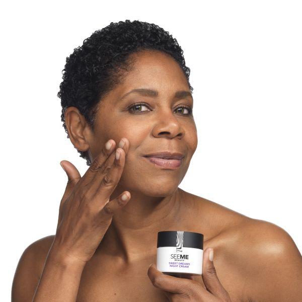 African American SeeMe Model applying sweet dreams night cream on her face