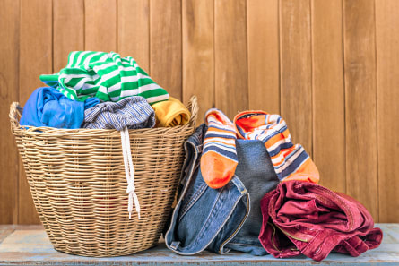 A pall of clothes in a laundry basket and on the floor