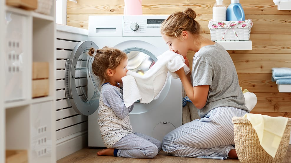 Woman and Child smelling clean towel that came out of the dryer