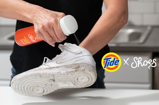 Man using a bottle of TideXShoe cleaner spray to clean his white shoes