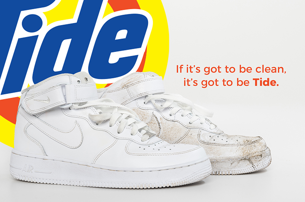 Banner with Tide Logo on the background and a pair of white shoes with the back shoe cover in dirt and the front one cleaned. With the wording on the banner If it's got to be clean, it's got to be Tide.