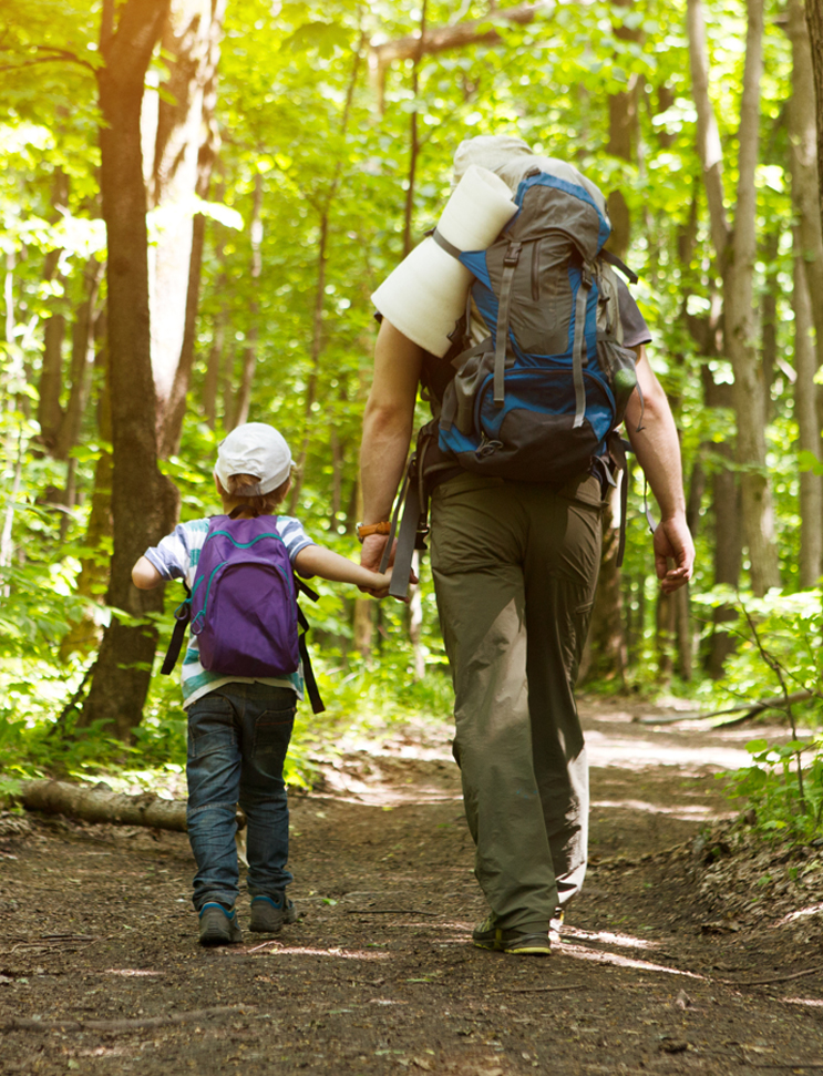 A father and daughter out hiking in the woods.