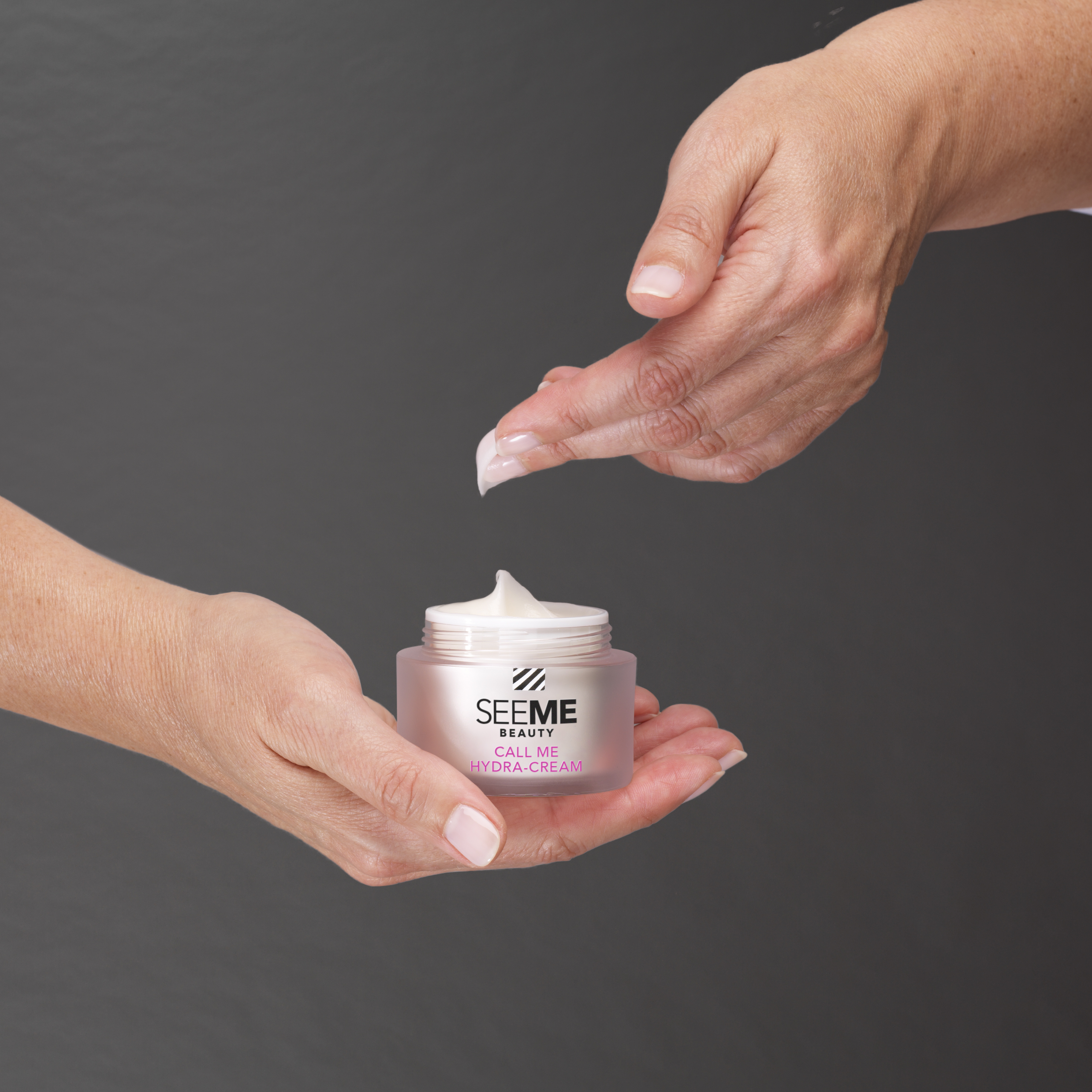 SeeMe Call Me Hydra-Cream with SeeMe Complex. Image of woman dipping the light airy moisturizer from the jar she is cradling in her hand