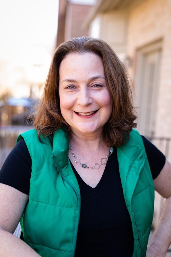 Erin Mantz wearing a block shirt and green vest