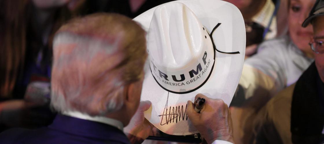 Donald Trump signs a Cowboy hat