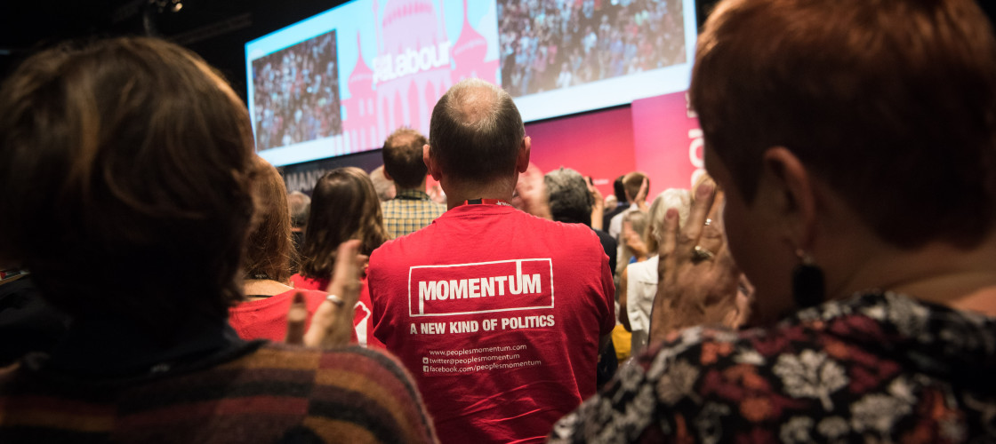A member of Momentum watches Jeremy Corbyn's speech at the Labour conference in Brighton