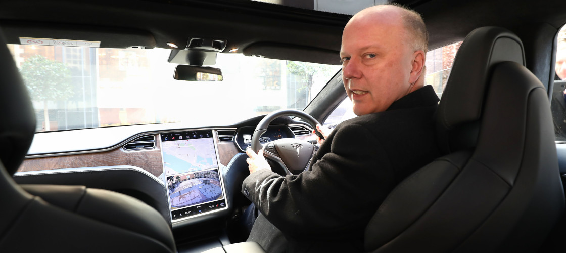 Transport Secretary Chris Grayling driving a Tesla S car