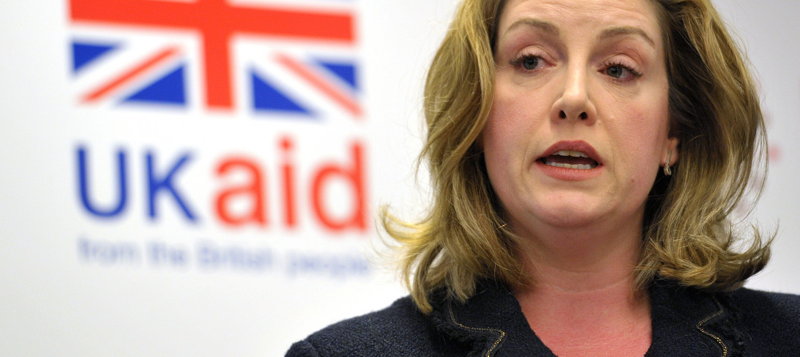 Penny Mordaunt stands behind a lectern at a UKAID event