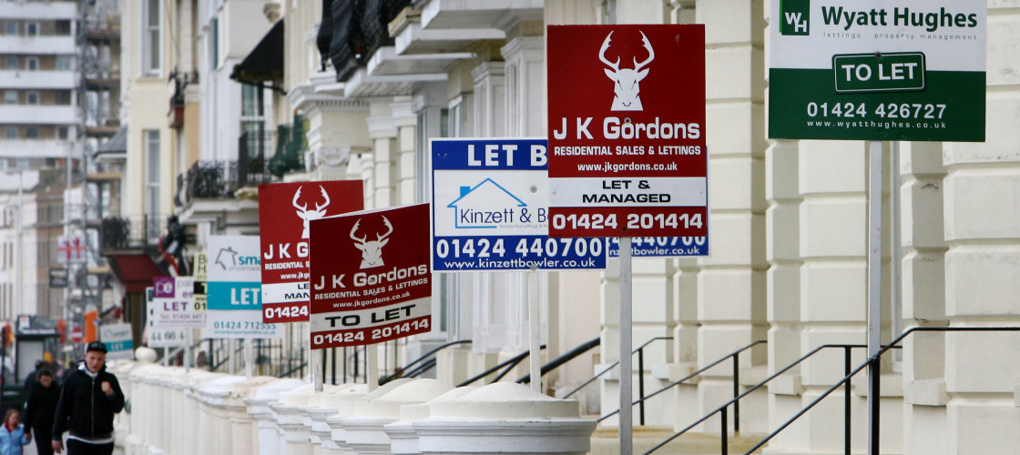 A row of buildings with For Let signs outside