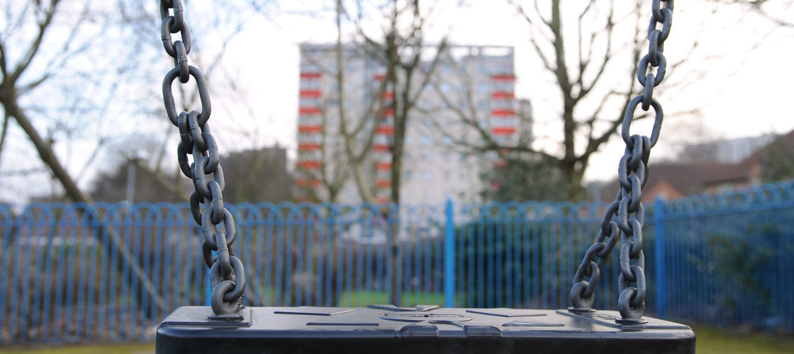 Image of swings in front of a tower block
