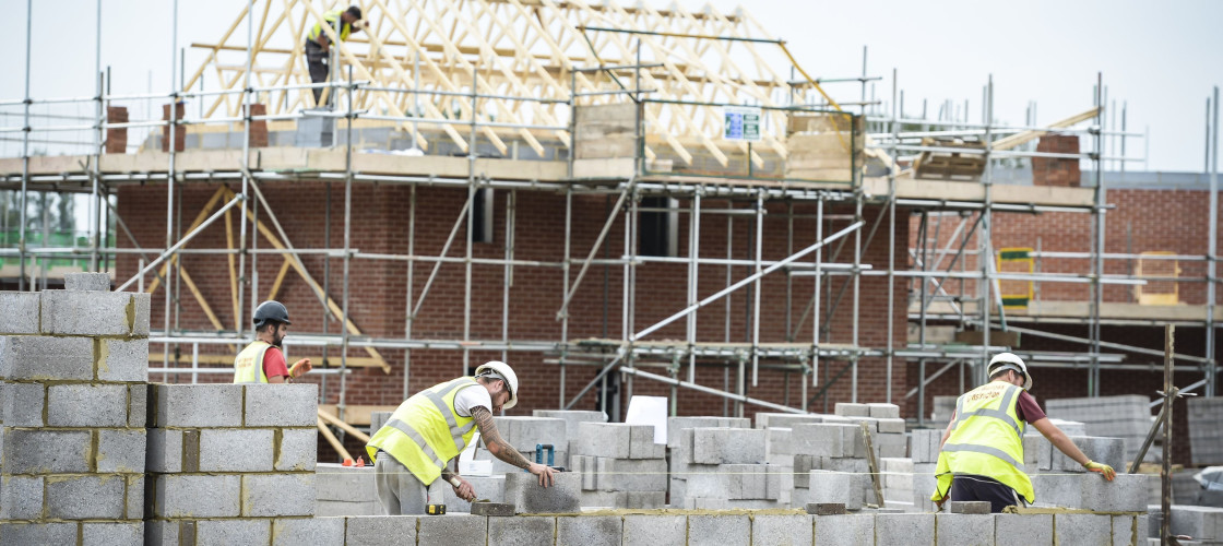 Builders lay blocks on a building site near Bristol,