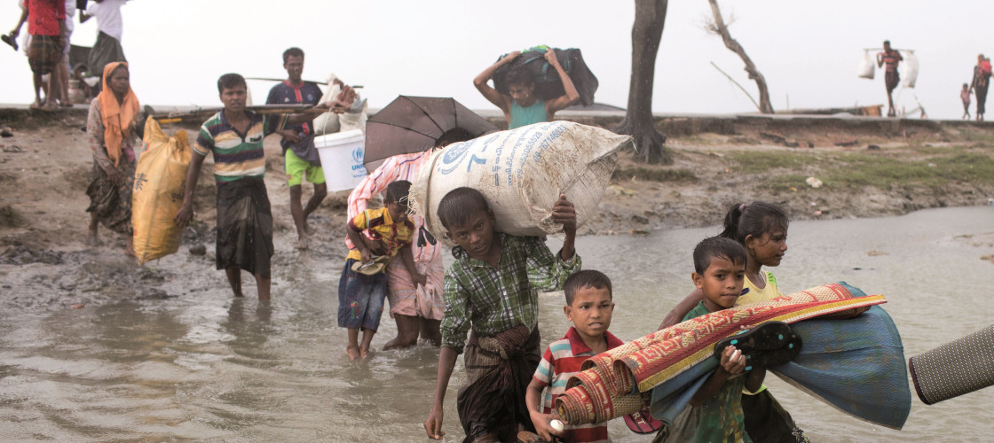 Young children and their families are carrying their possessions through a river in Rohingya