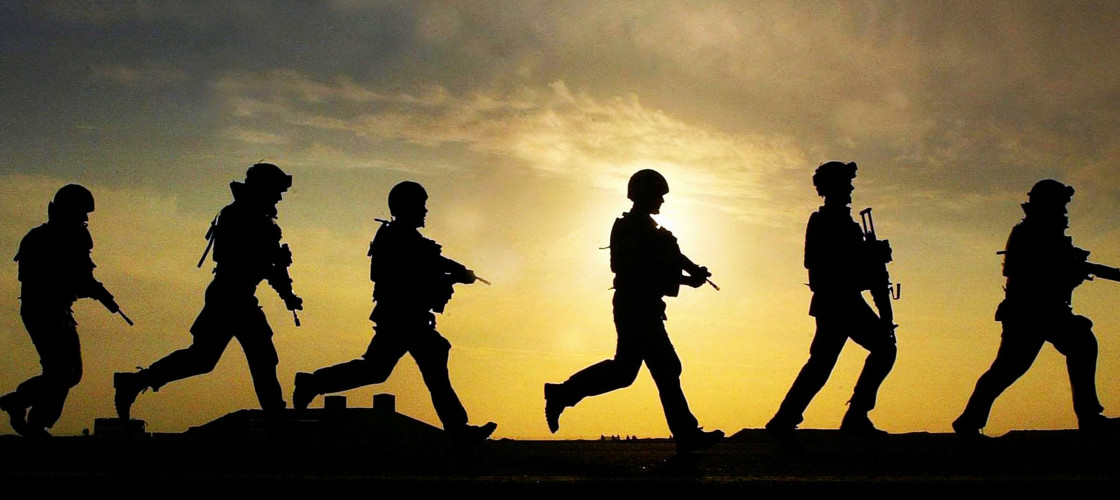 Soliders run across a hill at sunset