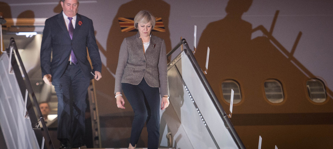 Theresa May and Liam Fox descend the steps of a plane in New Delhi