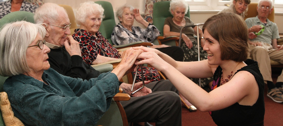 A woman conducts group music therapy with residents of a nursing home