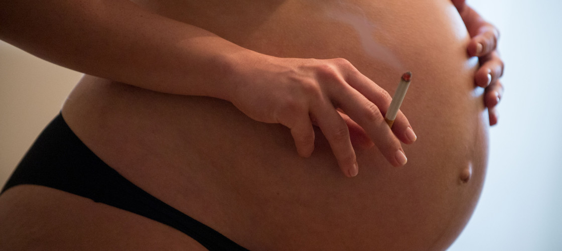 a pregnant woman holding a burning cigarette in her right hand