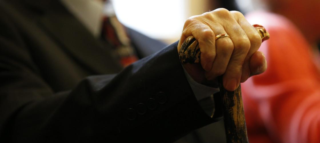 Elderly man holds a walking stick