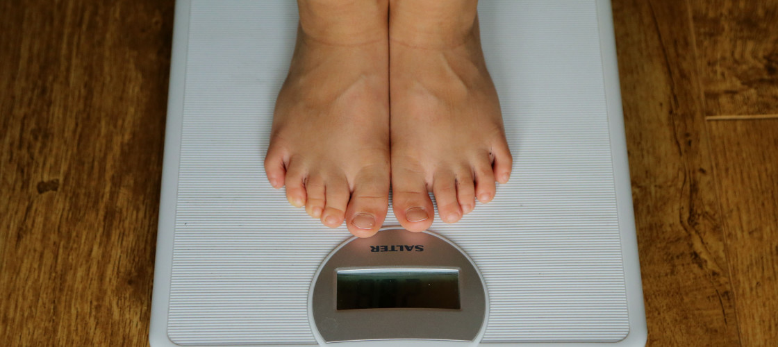 A person stands on a set of weigh scales