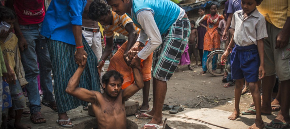 Suraj Ram, 22, a sanitation worker is helped out of a manhole after unblocking a drain in Yarpur Suraj Ram, 22, a sanitation worker is helped out of a manhole after unblocking a drain in Yarpur slum, Patna, Bihar, Indiaslum, Patna, Bihar, India