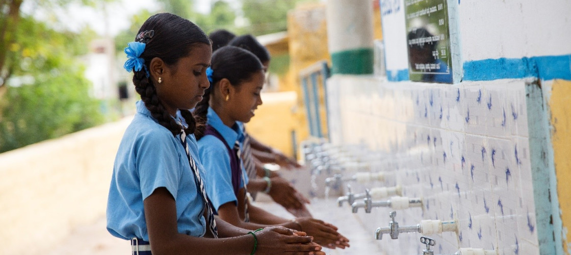A group of schools girls wash their hands