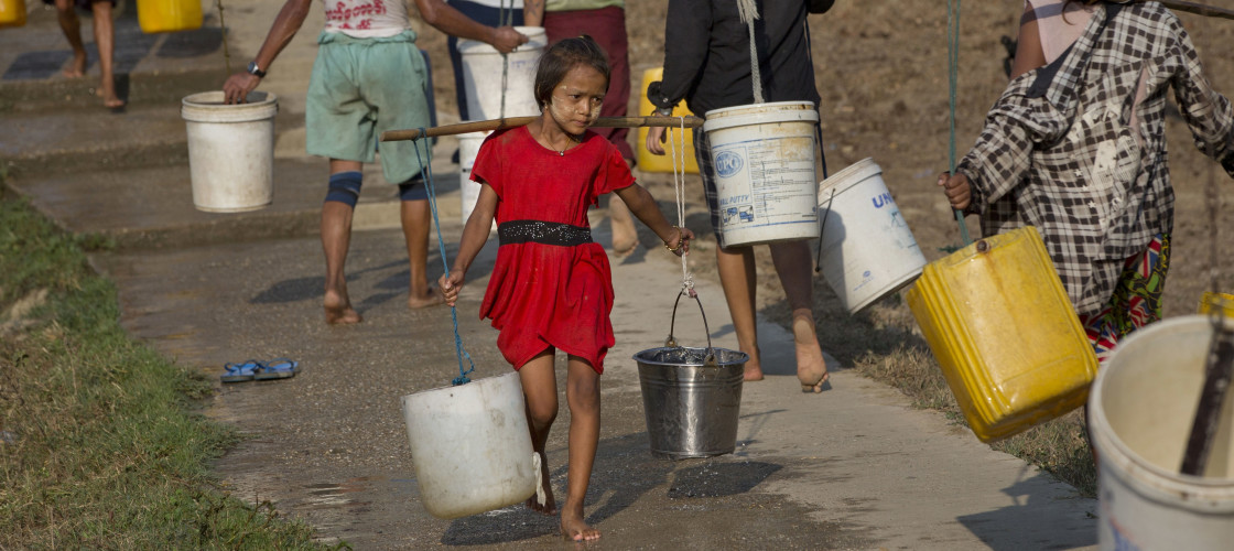 Moe La Htike, 8, center, carries drinking water collected from a pond in Dala township, south of Yangon, Myanmar