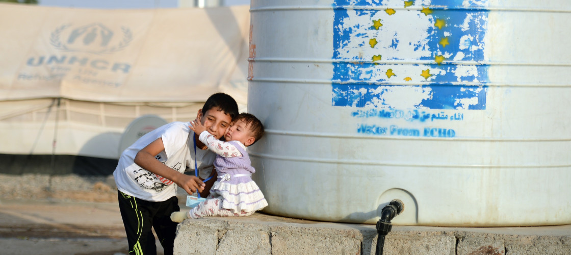 A boy carries his little sister to a water tank provided by UNICEF in the Debaga refugee camp between Mosul and Erbil, Iraq