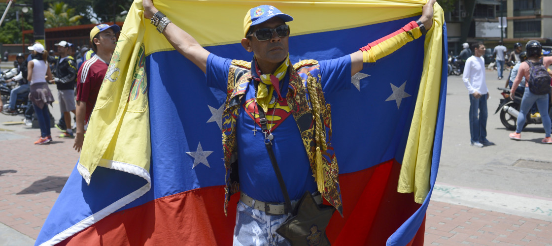 A protestor holds up a Venezuelan flag in Caracas, Venezuela, 30 July 2017. Opposition supporters protested against the constitutional assembly election.