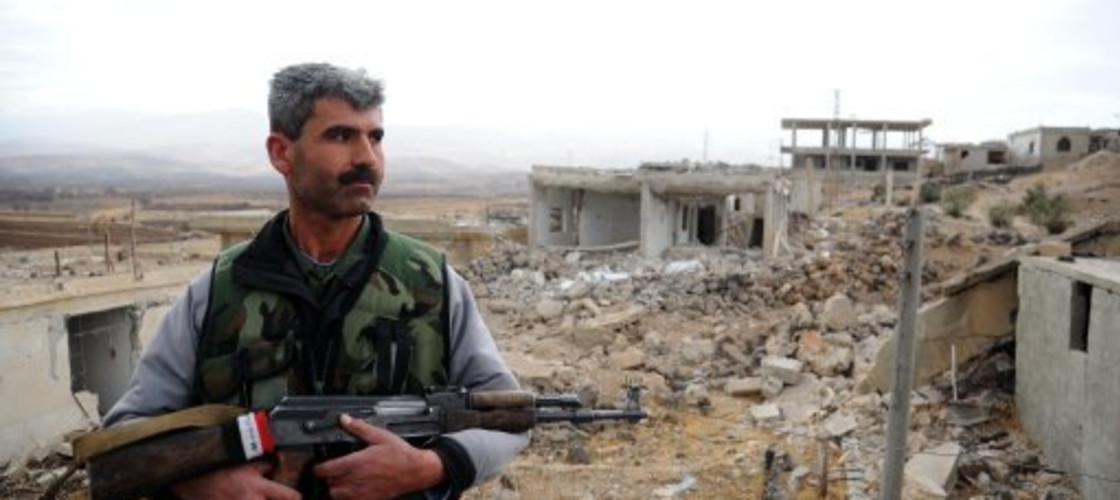A Syrian soldier holds a rifle in-front of a set of ruins