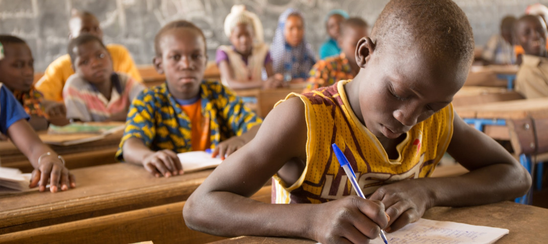 Djibril, schoolboy pictured in his classroom and writing on a notebook at school, Region of Mopti, in Mali