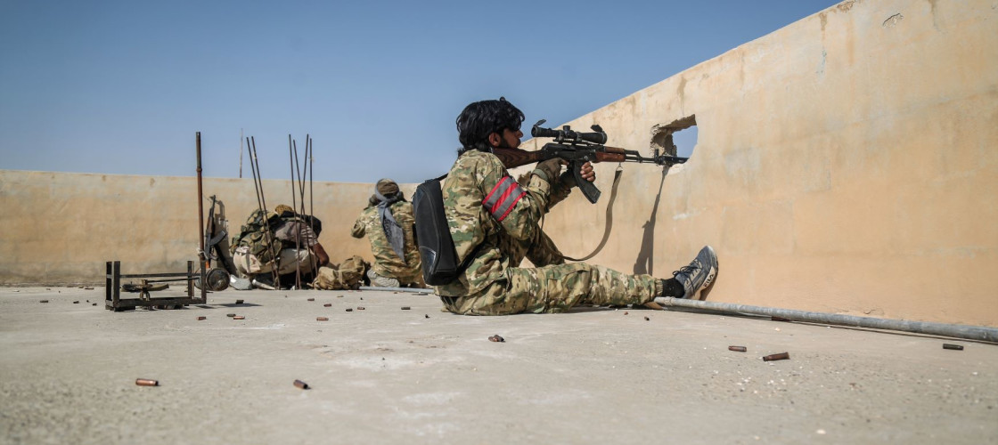 A sniper from the Turkish-backed Syrian National Army takes aim on a rooftop at Suluk town in the countryside of Tell Abiad after clashes with Kurdish fighters