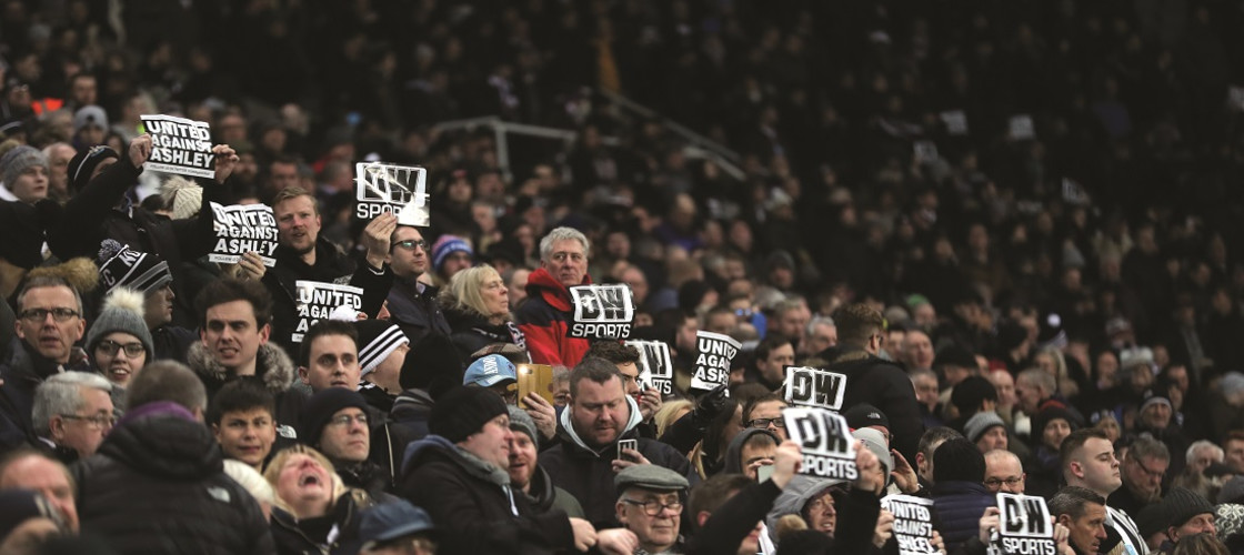 Newcastle United fans hold up banners in protest against owner Mike Ashley at St James' Park
