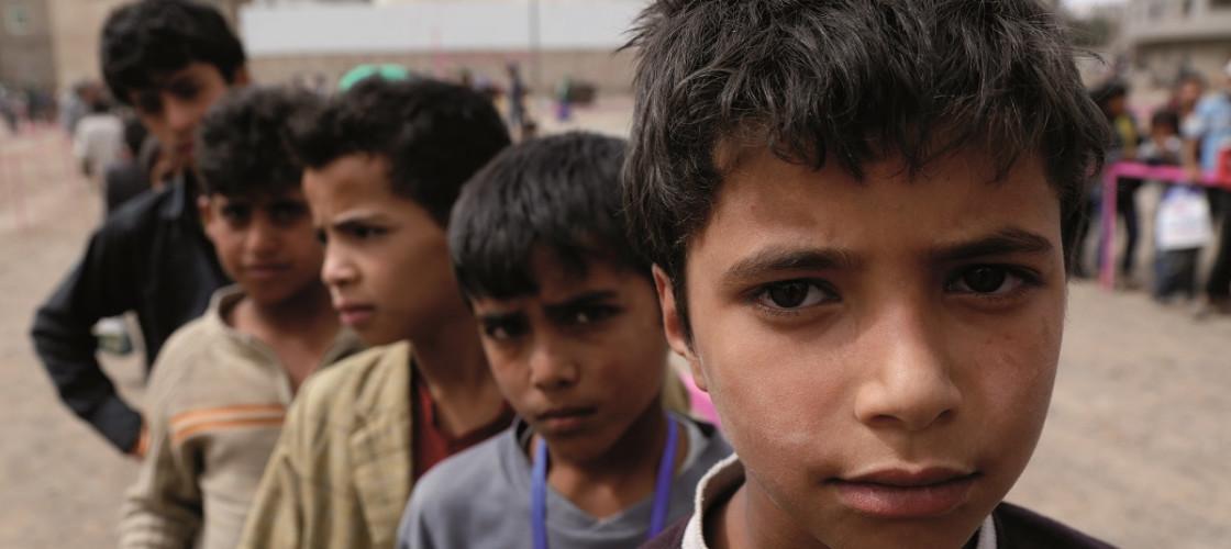 Yemeni children queue to receive food, in file