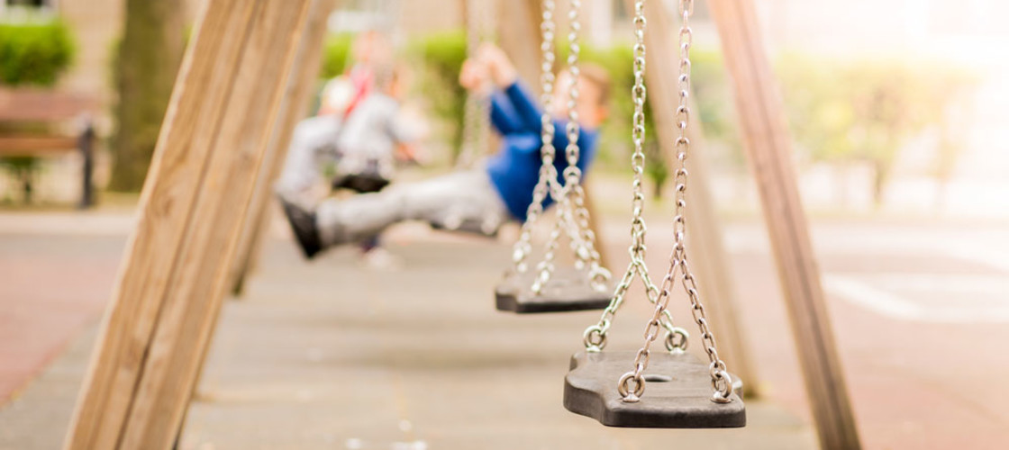 Empty chain swings in a playground. Blurred children swing behind.