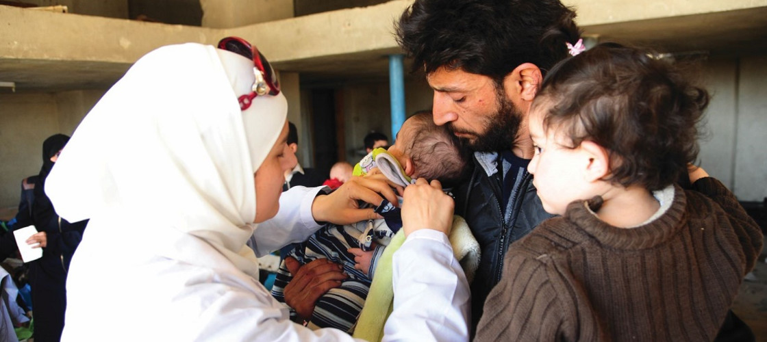 A doctor administers a vaccine to a child in war-torn Harasta city, Syria