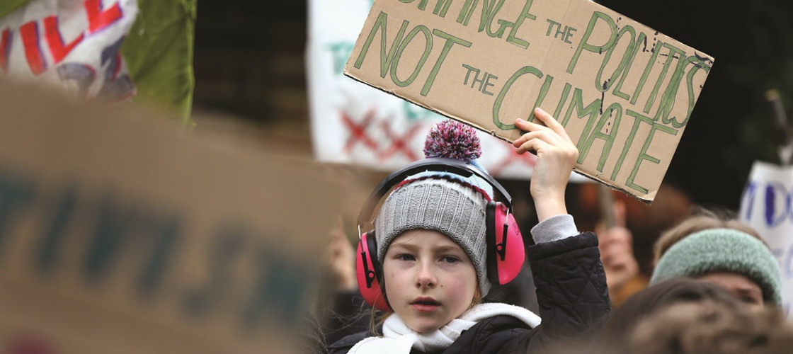 A climate protester holds up a sign reading 'Change the politics, not the climate'