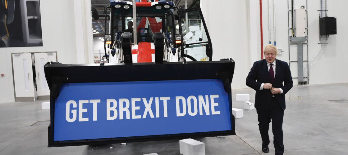 "Prime Minister Boris Johnson walks away after driving a Union flag-themed JCB, with the words ""Get Brexit Done"" inside the digger bucket, through a fake wall emblazoned with the word ""Gridlock"""