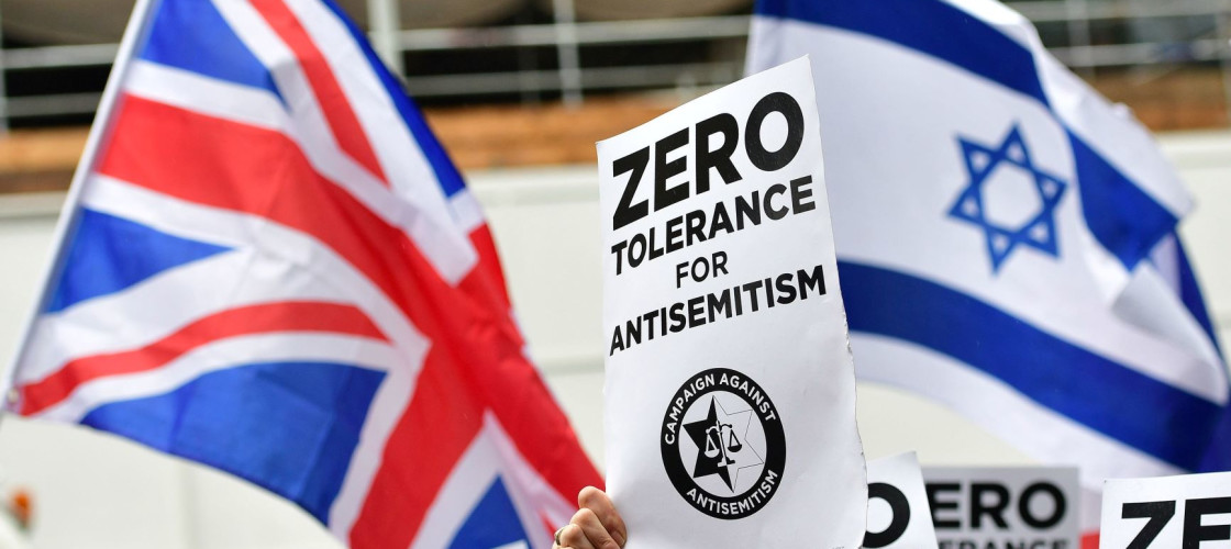 Signs reading 'Zero tolerance for antisemitism' in front of the Israeli and Union flag
