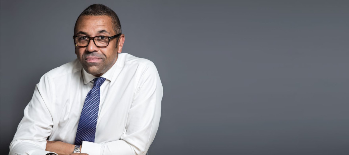 James Cleverly sits at one end of a long table, holding a pen