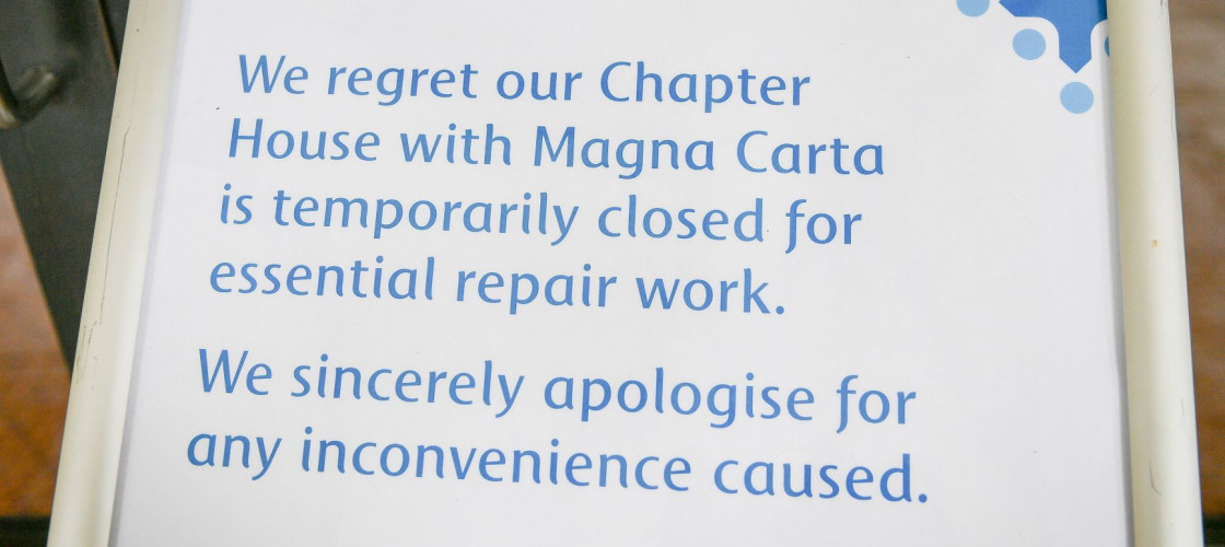 "A sign on a stand in Salisbury Cathedral reading ""We regret our Chapter House with Magna Carta is temporarily closed for essential repair work. We sincerely apologise for any inconvenience caused."""