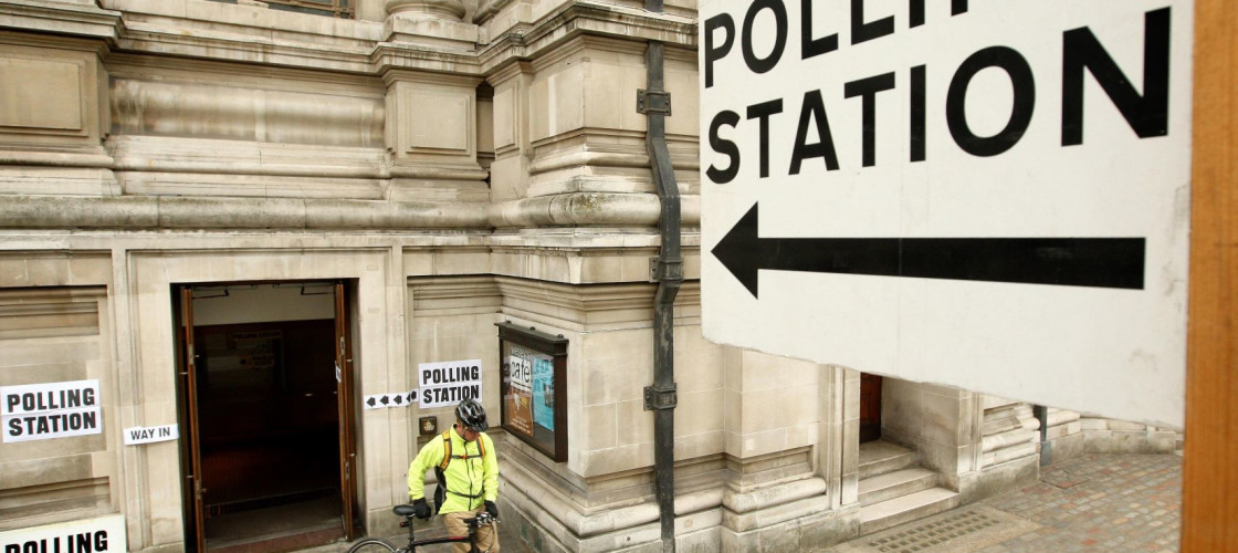 A large polling station sign points towards a door in a baroque style building, surrounded by several other polling station signs, as a man leaves pushing a bike