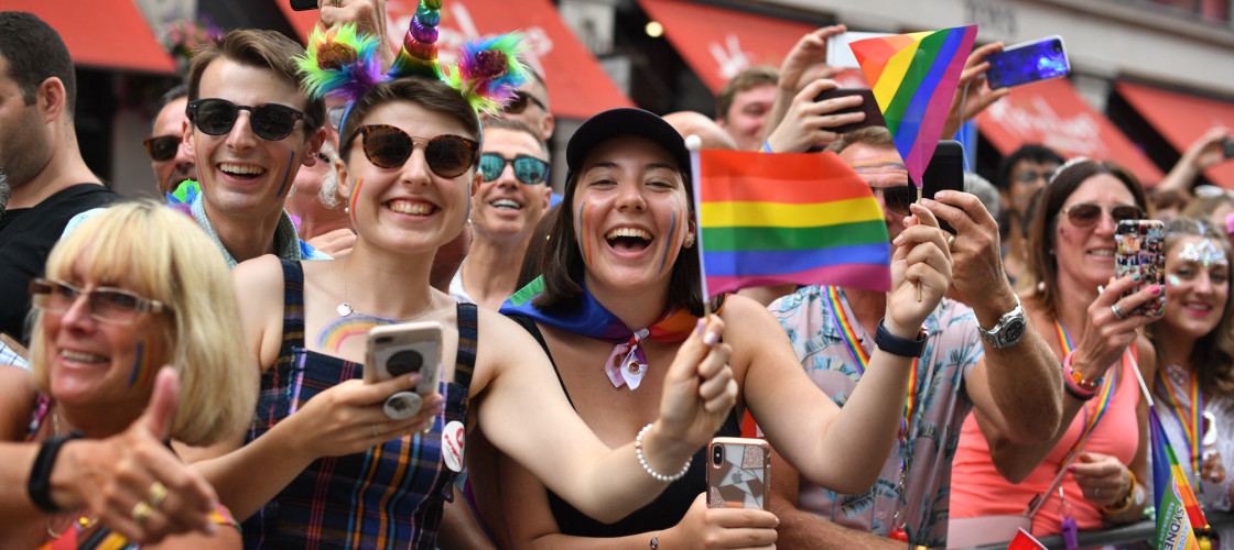 Young people celebrate London Pride with LGBT flags, face paint and a unicorn horn headband