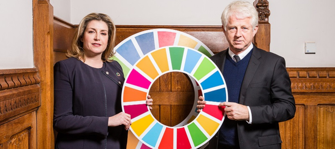 Penny Mordaunt and Richard Curtis holding a wheel depicting the 17 Sustainable Development Goals