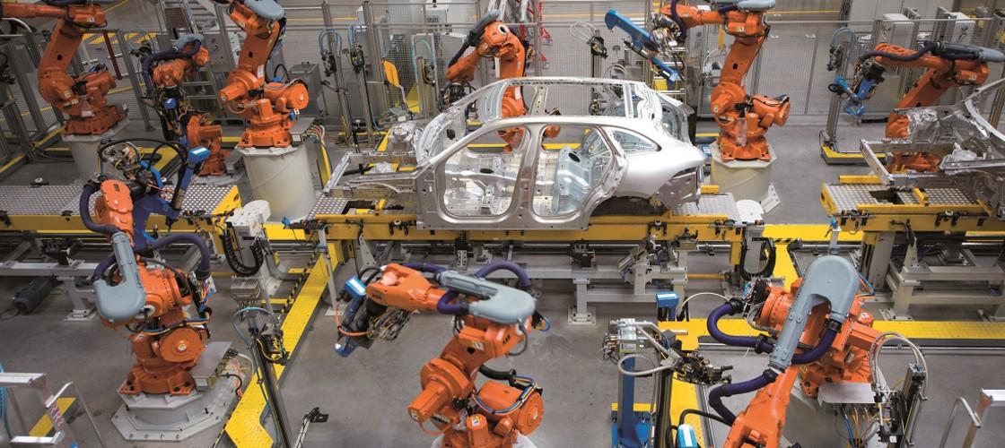 Robotic arms rivet car panels together