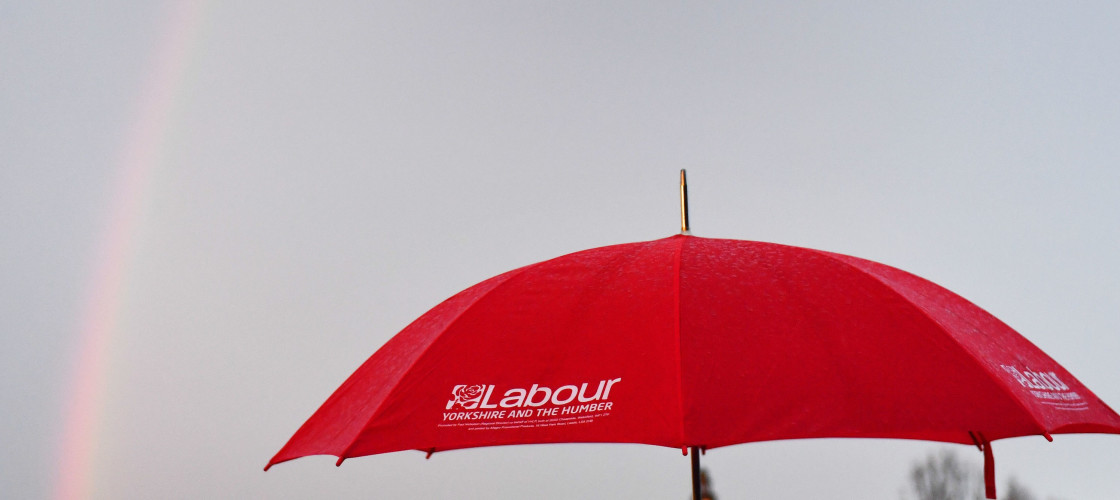 A Labour supporter holds an umbrella as a rainbow crosses the sky